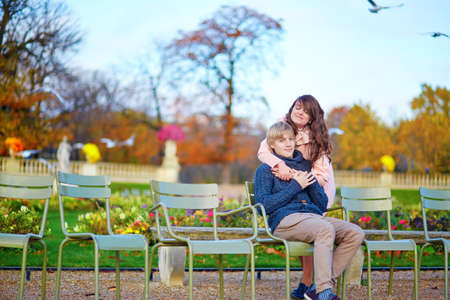 Young dating couple in the Luxembourg gardens of Paris on a bright fall day, sitting on green chairs near pond photo