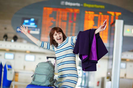 Beautiful young female passenger at the airport near the flight information board, happy and laughing, meeting someone or enjoying her vacation 版權商用圖片