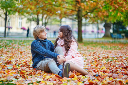 Young dating couple in Paris on a bright fall day sitting on the ground in autumn leaves photo
