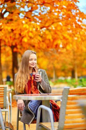 vin chaud: Belle jeune femme dans un café de la rue parisienne boire du vin chaud sur une belle journée d'automne coloré Banque d'images