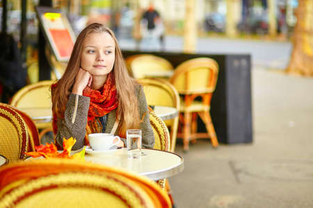 Beautiful young woman in a Parisian street cafe drinking tea or coffee on a beautiful colorful autumn day photo