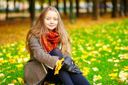 sitting on the ground: Beautiful young woman in Paris sitting on the ground on a beautiful colorful autumn day Stock Photo