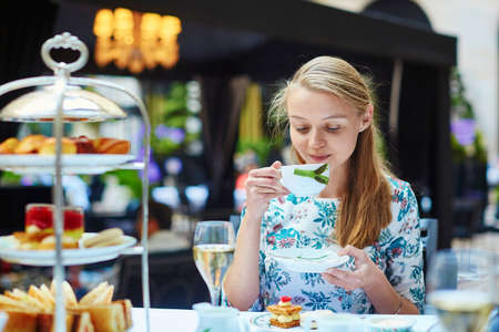 Beautiful young woman enjoying afternoon tea with selection of fancy cakes and sandwiches in a luxury Parisian restaurant Stock Photo - 41315276