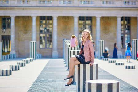 royale: Joven y bella mujer sentada en una de las Colonnes de Buren en Palais Royale en Par�s