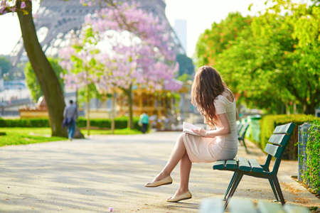Beautiful young woman in Paris, near the Eiffel tower on a nice and sunny spring day, reading on the bench outdoors Reklamní fotografie