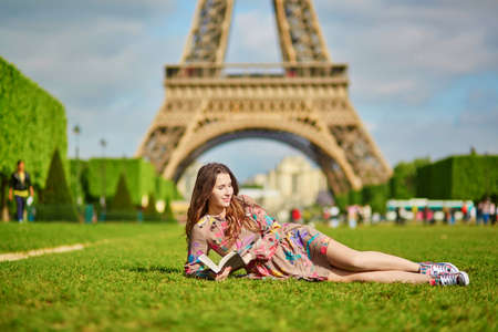 schoolgirl: Beautiful young woman walking in Paris lying on the grass near the Eiffel tower on a nice spring or summer day and reading a book. Student or schoolgirl doing her homework or preparing to exams Stock Photo