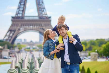 Gelukkig gezin van drie plezier samen in Parijs, nabij de Eiffeltoren