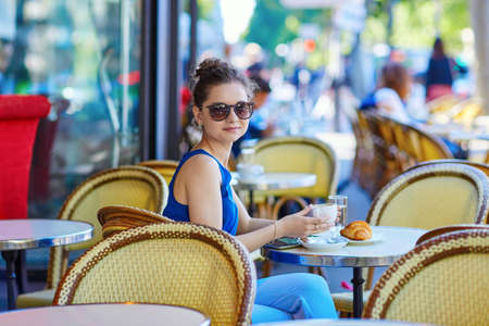 european: Beautiful young Parisian woman in blue blouse drinking coffee in an outdoor cafe on a summer day Stock Photo