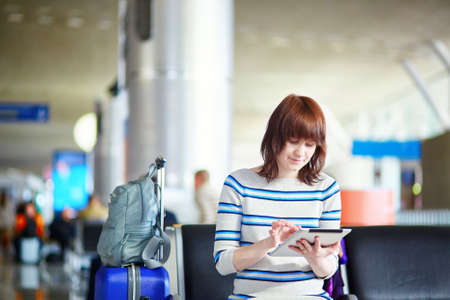 airplane girl: Young female passenger at the airport, using her tablet computer while waiting for her flight