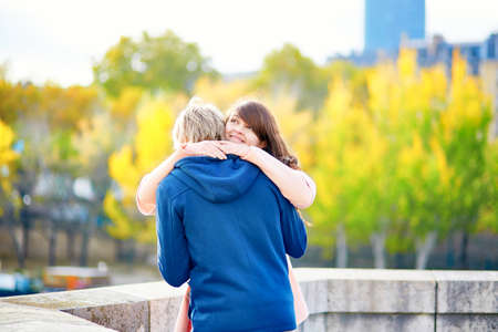 man woman hugging: Young dating couple in Paris on a bright fall day, walking together by the Seine, colorful autumn leaves in the background