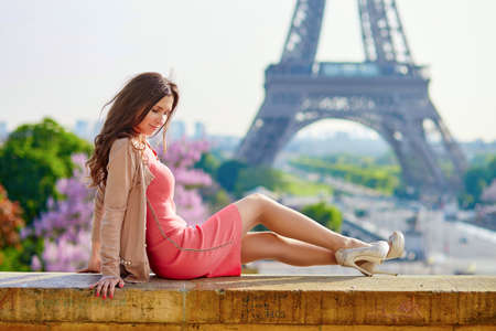 Eiffel Tower: Young beautiful and elegant Parisian woman in pink dress on the high heels sitting near the Eiffel tower in Paris Stock Photo
