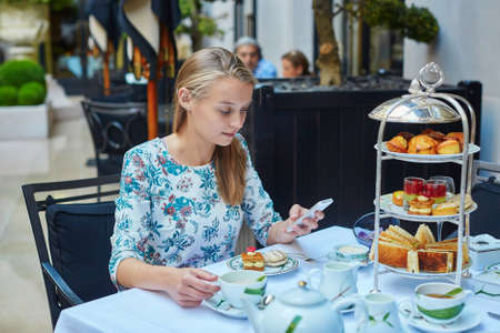 afternoon fancy cake: Beautiful young woman enjoying afternoon tea with selection of fancy cakes and sandwiches in a luxury Parisian restaurant