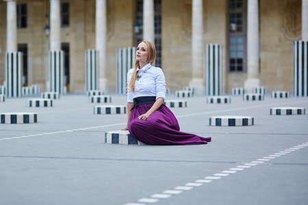 palais: Beautiful young woman sitting on one of the Colonnes de Buren in Palais Royale in Paris