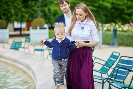 palais: Happy family of three in the beautiful garden of Palais Royal in Paris on a summer day Stock Photo