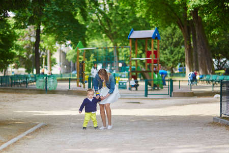 on playground: Beautiful young mother and her adorable toddler son having fun together on a Parisian playground, boy is kissing his mommy
