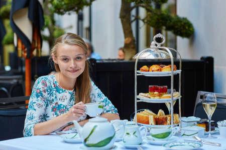럭셔리 파리 레스토랑에서 멋진 케이크와 샌드위치를 선택하여 오후의 차를 즐기고 아름다운 젊은 여성