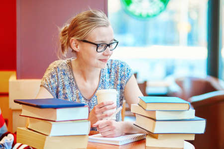 Beautiful young student with lots of books, studying or preparing for exams in a cafe. Shallow DOF