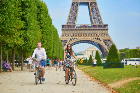 human relationships: Romantic couple riding bicycles near the Eiffel tower in Paris
