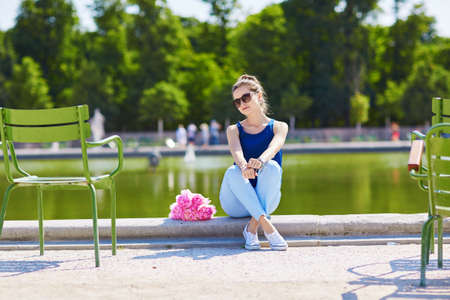 tube top: Beautiful young Parisian woman in blue tube top with bunch of pink peonies in the Tuileries garden of Paris Stock Photo