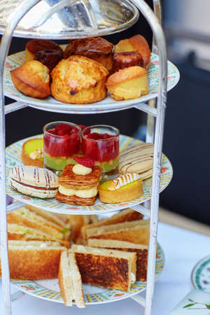 cakestand: Selection of sandwiches and fancy cakes served for the ceremony of afternoon tea on a cakestand Stock Photo