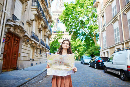 itinerary: Beautiful young tourist in long skirt on a street of Paris near the Eiffel tower on a summer day, looking at the map and planning her itinerary