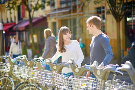 eco tourism: Happy romantic couple of tourists taking bikes for rent in Paris on a sunny day. Eco tourism and bicycle tourism concept Stock Photo