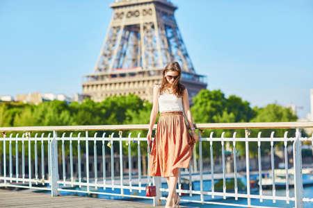 Schöne junge Pariser Frau in langen Rock in der Nähe des Eiffelturms an einem Sommertag