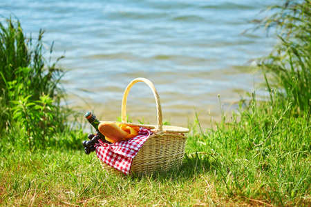 picnic blanket: Picnic basket with food and cider bottle near the water Stock Photo