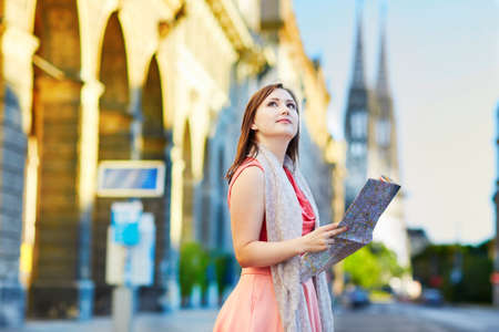 Beautiful young tourist using map in the street in Vienna, Austria