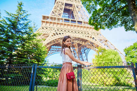 long skirt: Beautiful young Parisian woman in long skirt near the Eiffel tower on a summer day Stock Photo