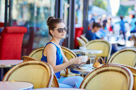 Beautiful young Parisian woman in blue blouse drinking coffee in an outdoor cafe on a summer day Stok Fotoğraf
