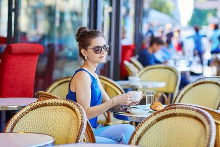 Mooie jonge Parijse vrouw in blauwe blouse koffie drinken op een terrasje op een zomerse dag
