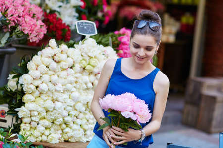 Beautiful young Parisian woman selecting pink peonies in French flower shop or at market