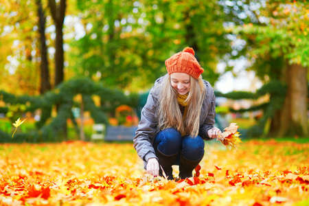 autumn young: Cheerful young girl gathering autumn leaves in park