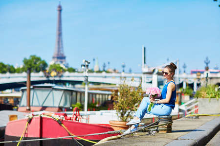 tube top: Beautiful young Parisian woman in blue tube top with bunch of pink peonies on the bank of the Seine, Eiffel tower is in the background