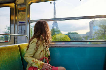 美しい若い女性パリの地下鉄の列車の旅とエッフェル塔の窓を通して見る