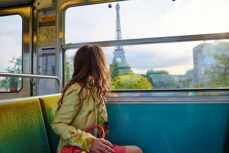 tren: Joven y bella mujer que viaja en un tren del metro de París y mirando por la ventana en la torre Eiffel