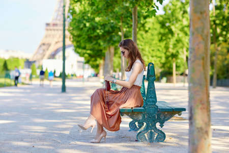 long skirt: Beautiful young Parisian woman in long skirt near the Eiffel tower on a summer day, sitting on the bench