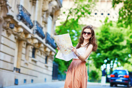 long skirt: Beautiful young tourist in long skirt on a street of Paris near the Eiffel tower on a summer day, looking at the map and planning her itinerary