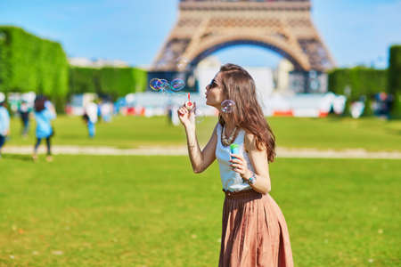Beautiful young woman in Paris blowing bubbles near the Eiffel tower on a summer day Imagens
