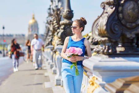 tube top: Beautiful young Parisian woman in blue tube top with bunch of pink peonies on the bank of the Seine