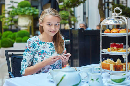 fancy cakes: Beautiful young woman enjoying afternoon tea with selection of fancy cakes and sandwiches in a luxury Parisian restaurant