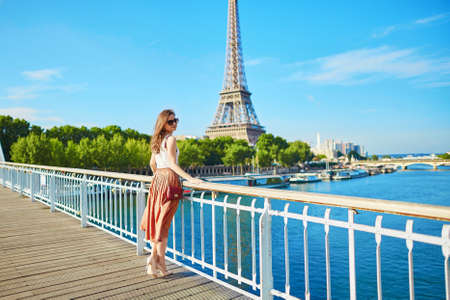 Beautiful young Parisian woman in long skirt near the Eiffel tower on a summer day Stock Photo