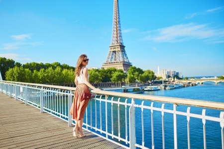 Mooie jonge Parijse vrouw in lange rok in de buurt van de Eiffeltoren op een zomerse dag Stockfoto