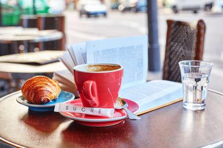 Ontbijt in een Parijse straatkoffie - kopje koffie, croissant en boek
