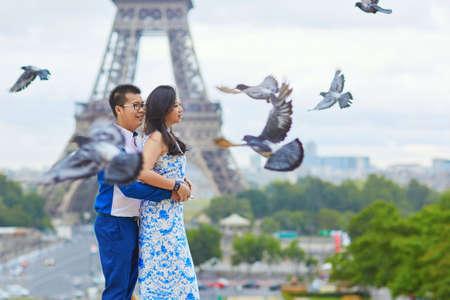 palomas volando: Joven romántica pareja abrazada asiático delante de la Torre Eiffel, París, Francia, con muchas palomas que vuelan alrededor de ellos Foto de archivo