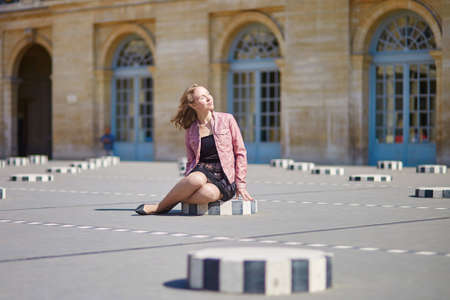 royale: Beautiful young woman sitting on one of the Colonnes de Buren in Palais Royale in Paris