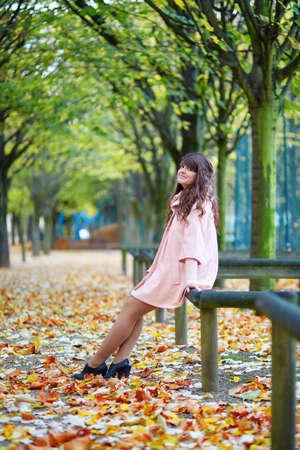 jardin de luxembourg: Beautiful young Parisian woman enjoying bright fall day in the Luxembourg garden of Paris, France