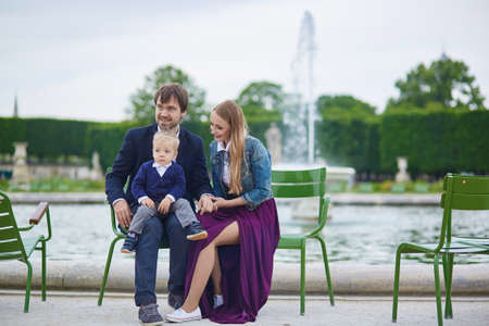 palais: Happy family of three in the beautiful garden of Palais Royal in Paris