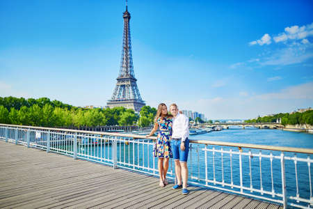 french kiss: Young romantic couple having a date and kissing near the Eiffel tower on a bridge over the Seine in Paris, France